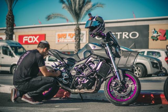 muž opravujúci motorku