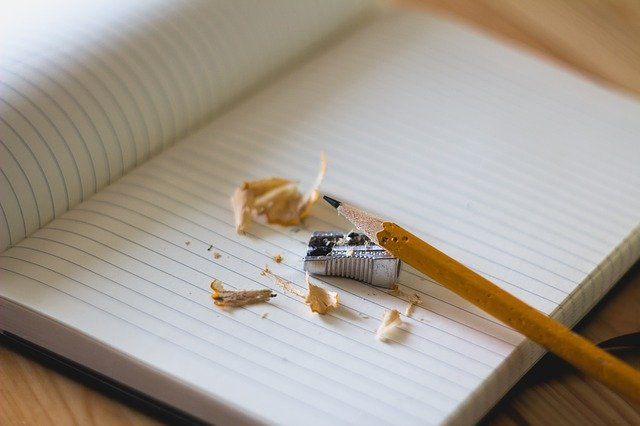 Ostrúhaná ceruzka a strúhadlo na poznámkovom zošite s riadkami