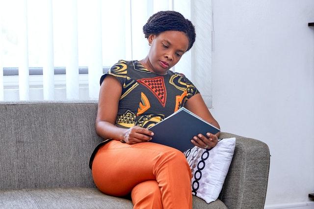 Žena sedí na gauči a pozerá do štósu papierov